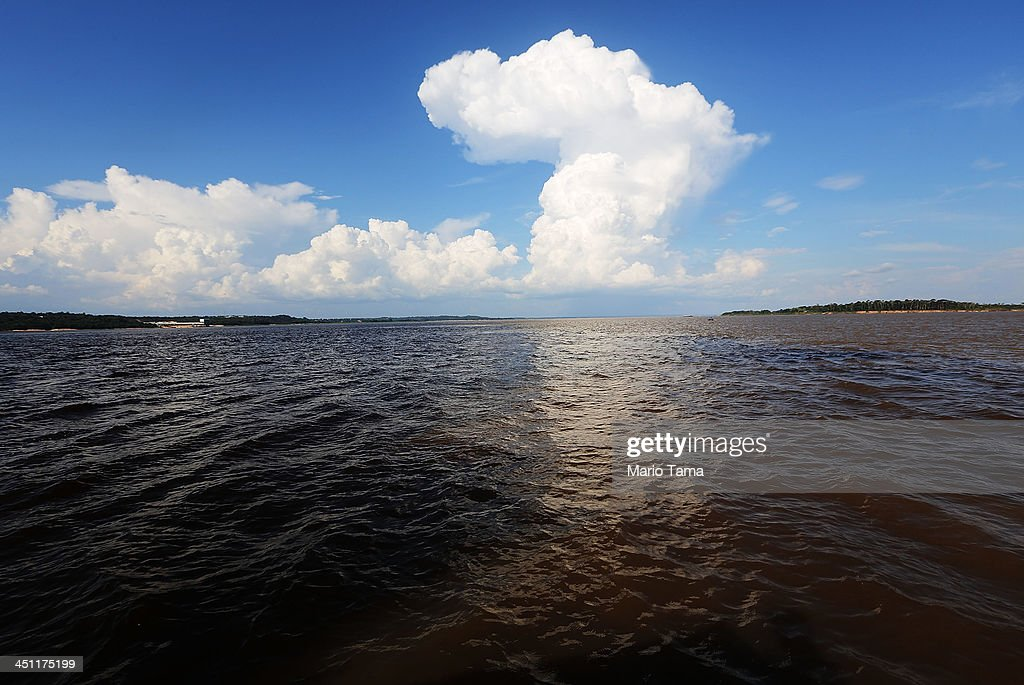 The famed 'Meeting of the Waters' where the Rio Negro and Rio Solimoes meet but appear to not mix sit below a cloud on November 21 2013 in Manaus...