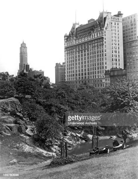 The famed Plaza Hotel rises from the trees in Manhattan's lovely Central Park New York New York c 1928 Five young men relax along the banks of The...