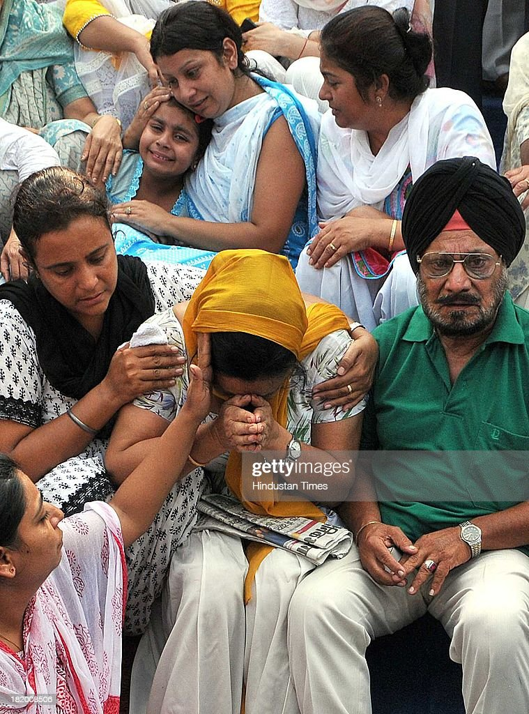 The family members of Lt Col Bikramjeet Singh, aged parents Major Paramjit Singh and Luvpreet Kaur, wife Navneet Kaur and daughter Ramneet mourn the loss at the cremation ground in Sector 25 on September 27, 2013 in Chandigarh, India. Army Chief General Bikram Singh and other senior officers of the Western Army Command paid their last respects to the martyred soul. Three terrorists sneaked across the border into Jammu and Kashmir and killed 10 people, including a Lieutenant Colonel of the Indian Army, in two audacious attacks yesterday. The militants, who were dressed in Army fatigues, first struck a police station in Hiranagar of Kathua district in Jammu, killing four cops and two others.