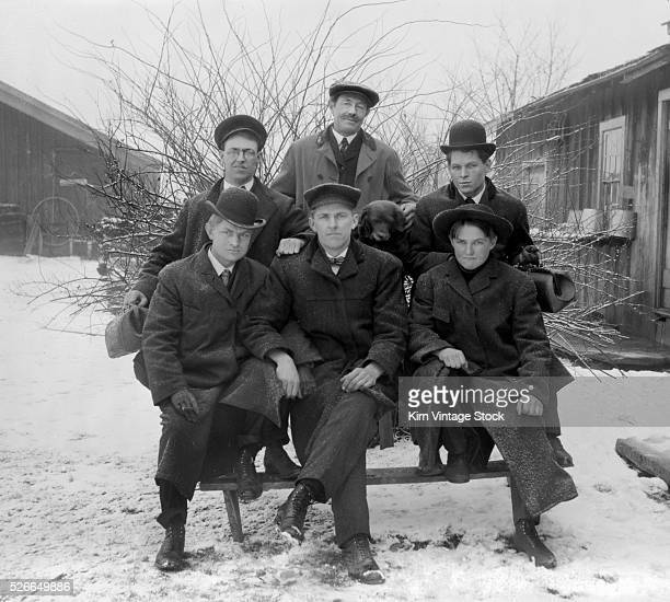 The family men sit for a portrait with their dog in the winter