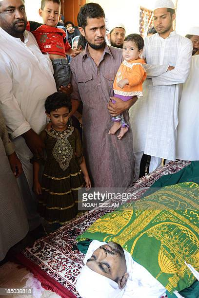 The family of Indian soldier Lance Naik Mohammed Feroz Khan look at his body during the funeral in Hyderabad on October 17 2013 Hundreds of mourners...