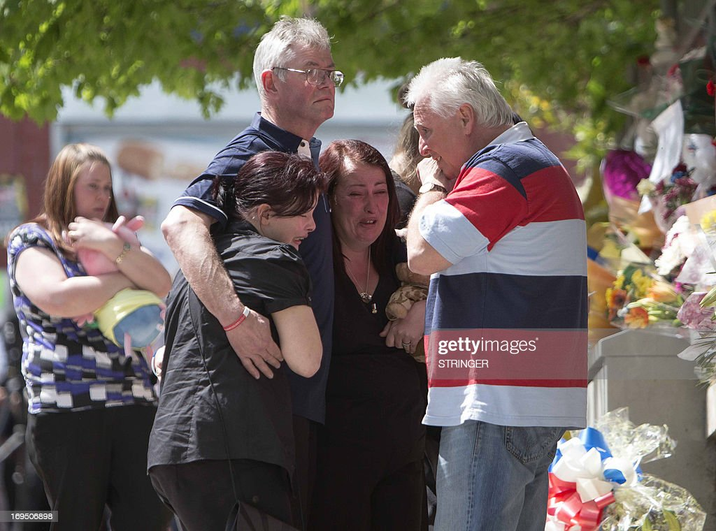The family of murdered British soldier Lee Rigby; (L-R) his wife Rebecca Rigby, his sister Sara McClure and his stepfather and mother Ian and Lyn Rigby, and father-in-law express their grief at the site of his death in Woolwich, east London on May 26, 2013. Drummer Lee Rigby, 25, who survived a tour of duty in Afghanistan, was butchered in broad daylight outside the Royal Artillery Barracks in Woolwich, southeast London.
