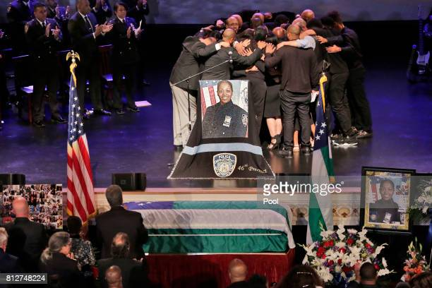 The family of Officer Miosotis Familia hug during her funeral at the World Changers Church July 11 2017 in The Bronx borough of New York City The...
