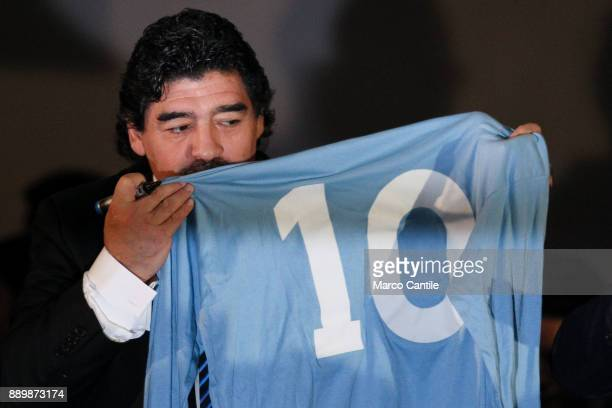 The famous football player Diego Armando Maradona kisses his football jersey when he played at Napoli during a press conference in Naples