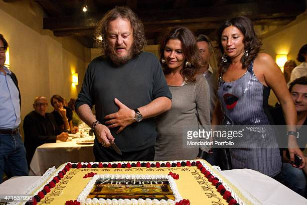 'The famous Italian singer Zucchero slices his birthday cake surrounded by the members of his staff and by his partner Francesca Mozer on his left...