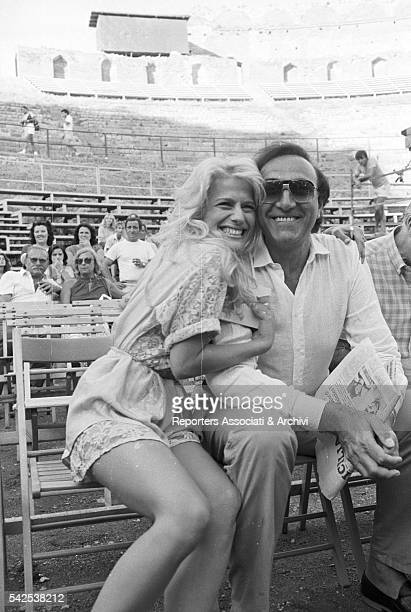 The famous Italian TV host Pippo Baudo with American actress and showgirl Heather Parisi sitting in the Greek theatre of Taormina during a beak of...