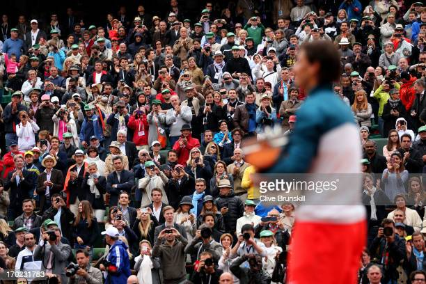 The fans applaud Rafael Nadal of Spain as he celebrates victory with the Coupe des Mousquetaires trophy in the men's singles final against David...