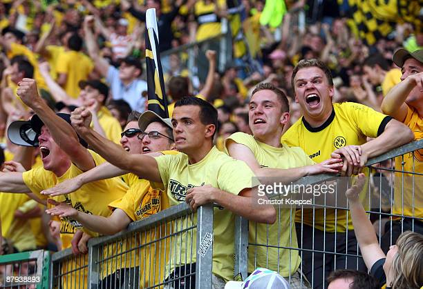 The fans of Dortmund celebrate their team during the Bundesliga match between Borussia Moenchengladbach and Borussia Dortmund at the Borussia Park on...