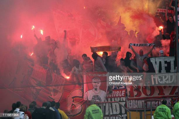The fans of Koeln throw smokebombs during the Bundesliga match between Borussia Moenchengladbach and 1 FC Koeln at Borussia Park on April 10 2011 in...
