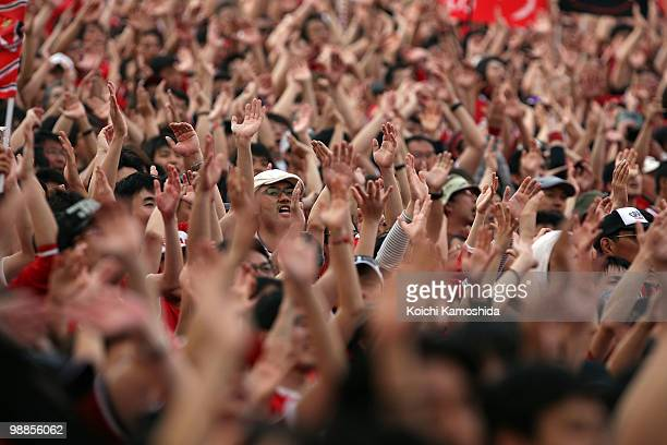 The Fans of Urawa Red Diamonds wave during the J League match between Urawa Red Diamonds and Nagoya Grampus at Saitama Stadium on May 5 2010 in...