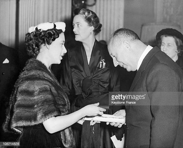 The Fashion Designer Christian Dior Receiving A Member Certificate Of The Red Cross From Princess Margaret Of England During A Reception Given At...