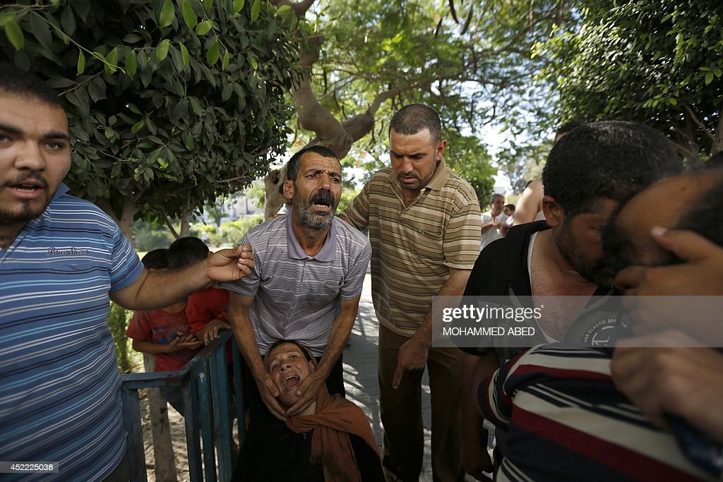 The father and mother of one of the four boys, all from the Bakr family, killed during Israeli shelling, react outside the al-Shifa hospital in Gaza City, on July 16, 2014. Four children were killed and several injured at a beach in Gaza City medics said, in Israeli shelling witnessed by AFP journalists. The strikes appeared to be the result of shelling by the Israeli navy against an area with small shacks used by fishermen. The deaths raised the overall toll in nine days of violence in Gaza to 213. AFP PHOTO / MOHAMMED ABED