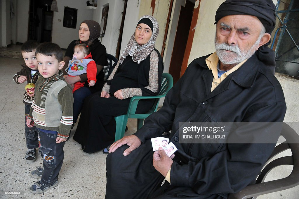 The father of Asaad Asaad, a Lebanese survivor of the migrant shipwreck in Indonesia last week, shows pictures before the arrival of his son at their home on October 6, 2013 in Akkar, an impoverished and remote province of north Lebanon. The 18 survivors, who returned to Lebanon, expressed their anger against the Lebanese state that they accuse of disregarding their difficulties with the influx of Syrian refugees. Assaad lost his wife and their 3 children.
