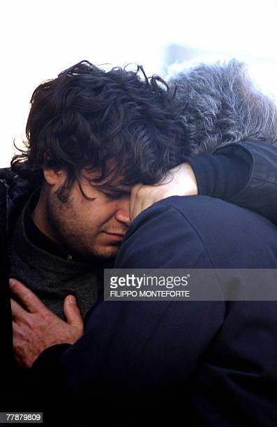 The father of Gabriele Sandri Giorgio embraces a friend of his son as people pay their respect to the corpse of the Lazio supporter in a mortuary...