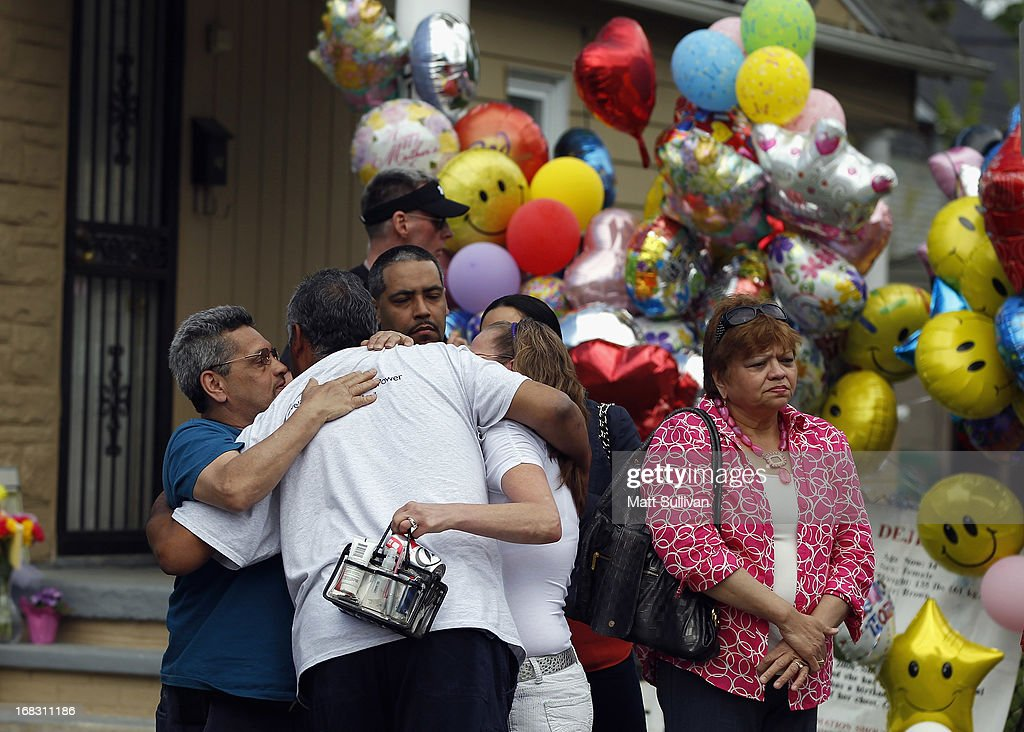 The father of kidnapping victim Gina DeJesus, Felix DeJesus (2L), hugs family members outside of their home during his daughter's homecoming on May 8, 2013 in Cleveland, Ohio. Gina DeJesus was one of three women who were held captive for almost a decade in a home in Cleveland, Ohio. Amanda Berry, Gina DeJesus, and Michelle Knight managed to escape their captors on May 6, 2013. Three suspects, brothers Ariel, Pedro and Onil Castro, were taken into custody in connection with the crime.