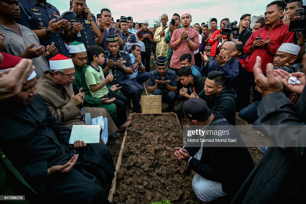 The father of Muhammad Aidil Aqmal (3rd L) and family members pray for his daughter during a mass funeral ceremony at the Raudhatul Sakinah cemetery for victims of the religious school Darul Quran Ittifaqiyah after a fire broke out yesterday on September 15, 2017 in Kuala Lumpur, Malaysia. A fire at the religious school in the Malaysian capital killed almost two dozen people including 21 students and two teachers.