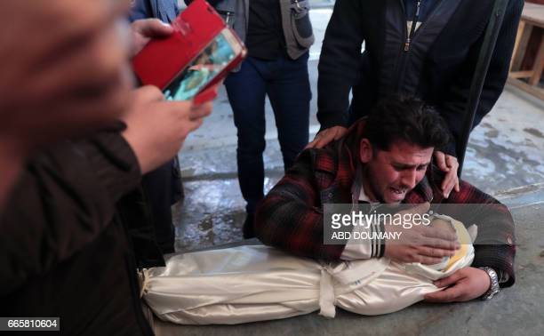 The father of oneyearold infant Amira grieves over her body as others wrap the burial shrowd in a makeshift morgue after she died in a reported air...