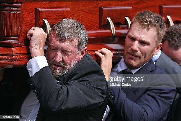 The father of Phillip Hughes Gregory Hughes carries the coffin with Australian cricket cricketer Aaron Finch who cries during the Funeral Service for...