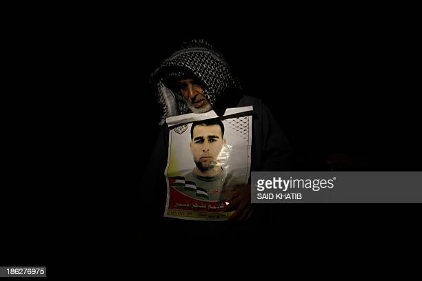 The father of released Palestinian prisoner Hazem Shubeir holds a poster of his son early on October 30 2013 prior to his arrival at his home in Khan...