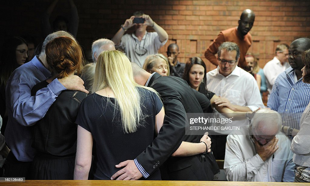 The father of South African Olympic sprinter Oscar Pistorius Henke reacts as relatives comfort each other on February 19 2013 after the athlete's...