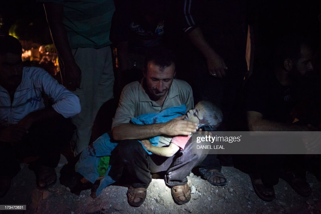 The father of three-year-old Khaled Baour weeps as he holds the body of his son who was killed alongside his older sister Safia, 14, after a shell landed on their family home while they gathered to break their fast with the iftar meal, prior to their burial late on July 13, 2013 in Maaret Al-Numan in Syria's southern Idlib province. The conflict in Syria began in 2011, with peaceful demonstrations calling for regime change but morphed into an insurgency after the regime unleashed a crackdown on dissent.
