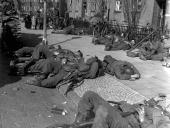 The fatigued Ninth Army after their nonstop drive towards Berlin lying on the pavement of a newly captured German town