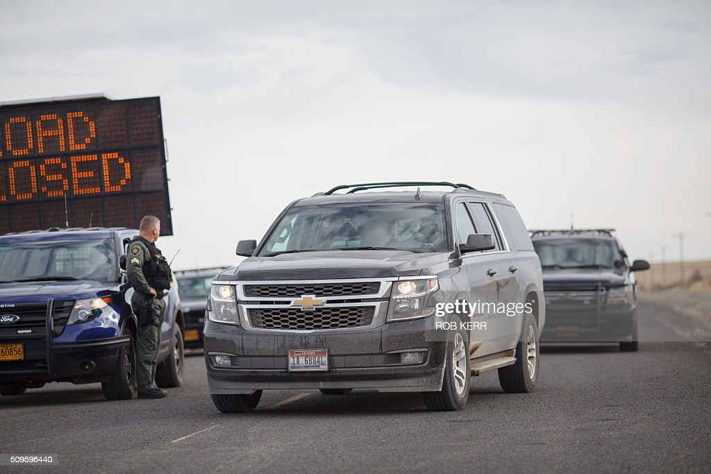 The FBI and Oregon State Police vehicles race past a road block leaving the Malheur Wildlife Refuge Headquarters near Burns, Oregon, on February 11, 2016. The FBI surrounded the last protesters holed up at a federal wildlife refuge in Oregon amid reports they will surrender on Thursday, suggesting the weeks-long armed siege is approaching a climax. / AFP / Rob Kerr