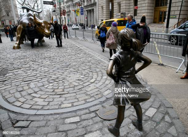 The 'Fearless Girl' statue a fourfoot statue of a young girl defiantly looks up the iconic Wall Street 'Charging Bull' sculpture in New York City...