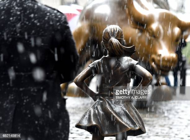 The ' Fearless Girl ' statue on Wall Street is seen as snow falls in New York March 10 2017 / AFP PHOTO / TIMOTHY A CLARY