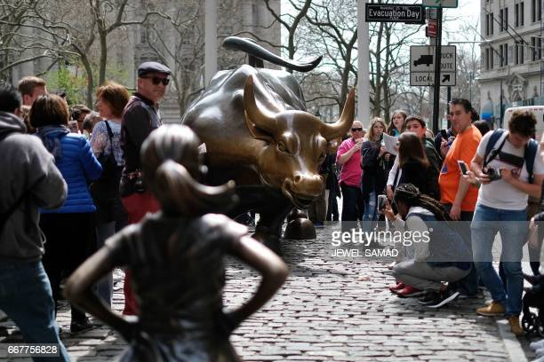 The 'Fearless Girl' statue stands facing the 'Charging Bull' as tourists take pictures in New York on April 12 2017 A battle is heating up between...