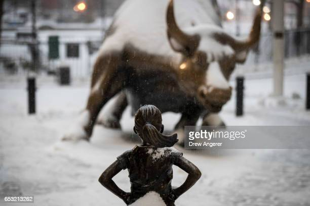 The 'Fearless Girl' statue stands in the snow and wintry mix in the Financial District March 14 2017 in New York City The blizzard warning for New...