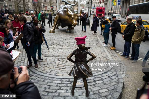 'The Fearless Girl' statues stands across from the iconic Wall Street charging bull statue March 8 2017 in New York City State Street Global Advisors...