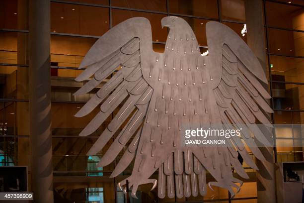 The Federal Eagle is seen during a session of the German Bundestag in the Reichstag building in Berlin on December 17 2013 Angela Merkel head of the...