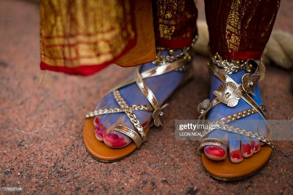 The feet of a devotee wearing a costume representing the Hindu god Lord Krishna are seen during the 'Ratha-yatra' Festival of Chariots, as the procession travels through central London on June 9, 2013. Now in it's 45th years, the procession sees thousands of Hare Krishna devotees pull three brightly decorated chariots bearing the Hindu dieties of Lord Jagannatha, Lady Subhadra and Lord Balarama from Hyde Park to Trafalgar Square. AFP PHOTO/Leon NEAL