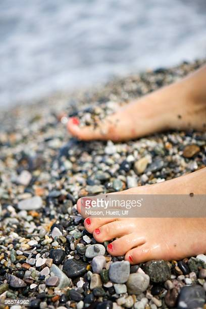 The feet of a girl on a pebbled beach, Italy.