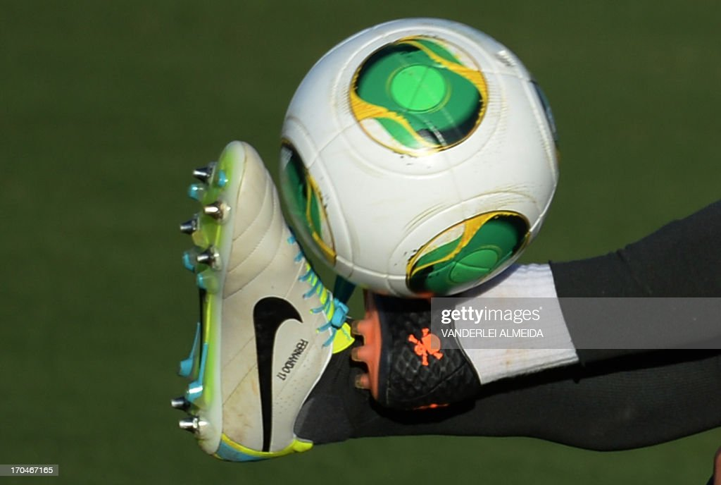 The feet of Brazilian national players Neymar (top) and Fernando (wjite shoe) as they vie for the ball during a training session in Brasilia, on June 13, 2013. Brazil will face Japan, Italy and Mexico in the Group A of the Confederations Cup.