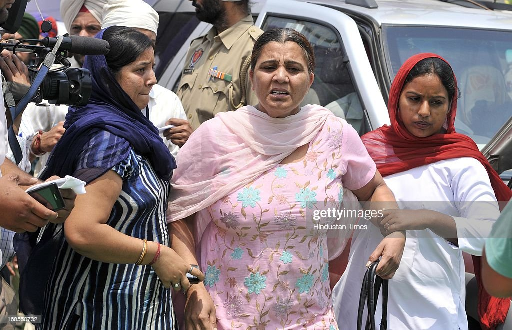 The female constable of Punjab Police in civil dress carries away, Prisoner of War PoW of 1971 war, Joginder Singh's daughter Harjit Kaur, who started raising her voice to free her father from Pakistani Jail during the bhog ceremony of Indian prisoner Sarabjit Singh at his native village in Bikhiwind on May 11, 2013 in Amritsar, India. In the presence of CM Punjab Parkash Singh Badal and former Union Minister Ambika Soni she demanded swift action in the case of other Indian prisoners locked in Pakistani Jails. Sarabjit Singh died on May 2, after a deadly attack by Pakistani inmates in Pakistan's Kot Lakhpath Jail in Lahore.