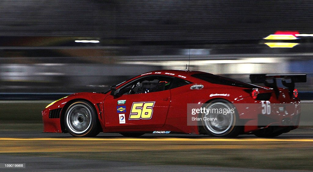 The #56 Ferrari 458 of Michael Waltrip, Robert Kauffman, Clint Bowyer, and Rui Aguas is shown in action at night during preseason testing at Daytona International Speedway on January 5, 2013 in Daytona Beach, Florida.