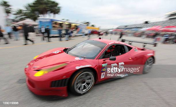 The Ferrari 458 of Michael Waltrip Robert Kauffman Clint Bowyer and Rui Aguas drives through the paddock during preseason testing at Daytona...