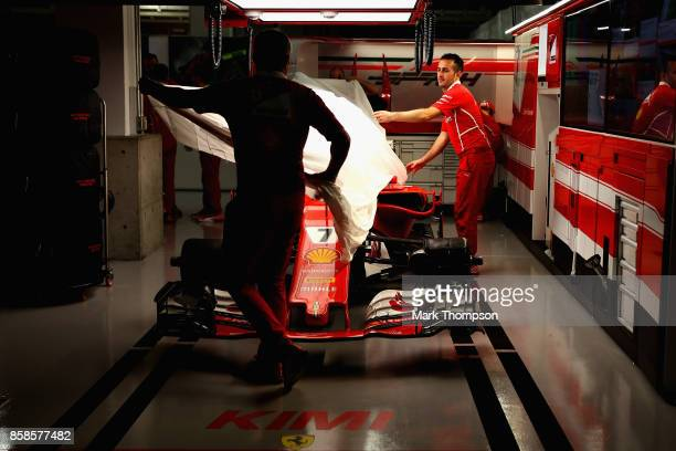 The Ferrari team cover the car of Kimi Raikkonen of Finland and Ferrari in the garage after qualifying for the Formula One Grand Prix of Japan at...