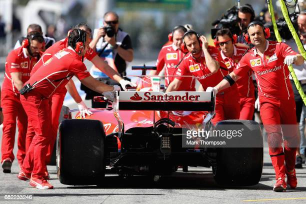 The Ferrari team push Sebastian Vettel of Germany and Ferrari in the Pitlane during practice for the Spanish Formula One Grand Prix at Circuit de...