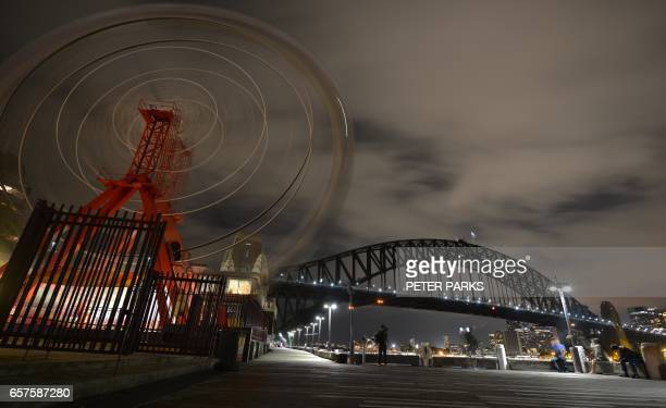 TOPSHOT The ferris wheel at Luna Park and Sydney Harbour Bridge are plunged into darkness for the Earth Hour environmental campaign in Sydney on...