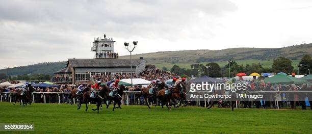 The field makes its way around the course during the Wicks Waste Services Juvenile Hurdle at Cartmel Racecourse Cartmel Cumbria