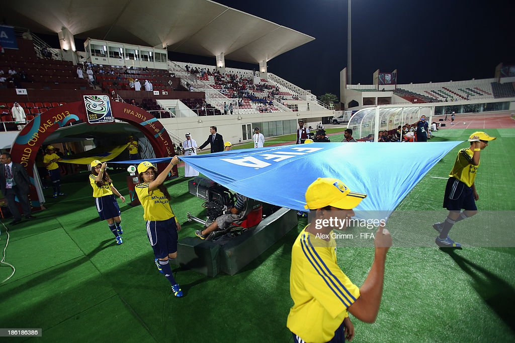 The FIFA flag is carried on the pitch prior to the FIFA U-17 World Cup UAE 2013 Round of 16 match between Honduras and Uzbekistan at Sharjah Stadium on October 28, 2013 in Sharjah, United Arab Emirates.