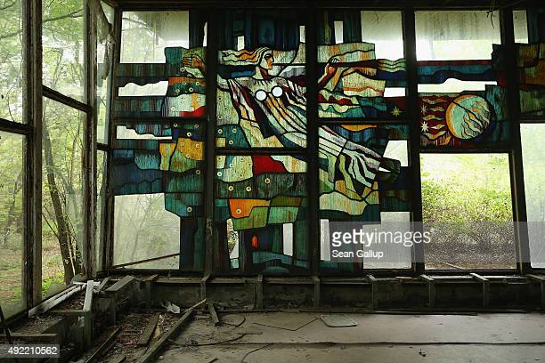 The figure of a woman decorates a stainedglass window in an abandoned riverside cafe on September 30 2015 in Pripyat Ukraine Pripyat lies only a few...