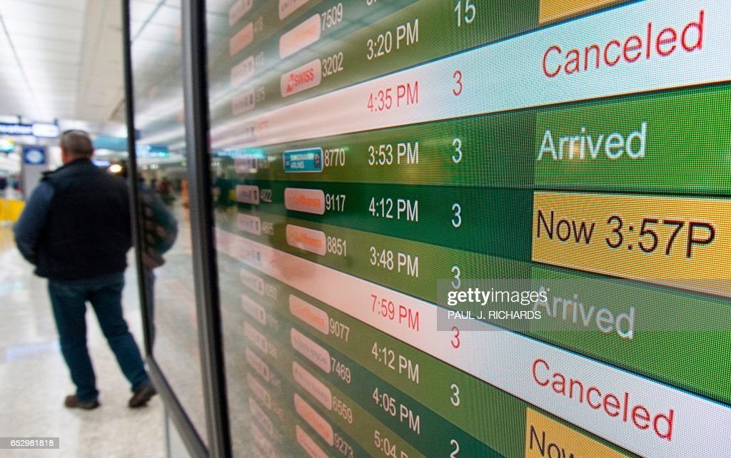 The filght status board is seen at Dulles International Airport (IAD) in Chantilly, Virginia, outside Washington, DC, March 13, 2017, as flights are cancelled in advance of an approaching large snow storm. Millions of Americans braced for potentially the worst winter storm of the season with blizzards forecast to dump up to two feet of snow on the East Coast, closing schools and spelling travel chaos. /