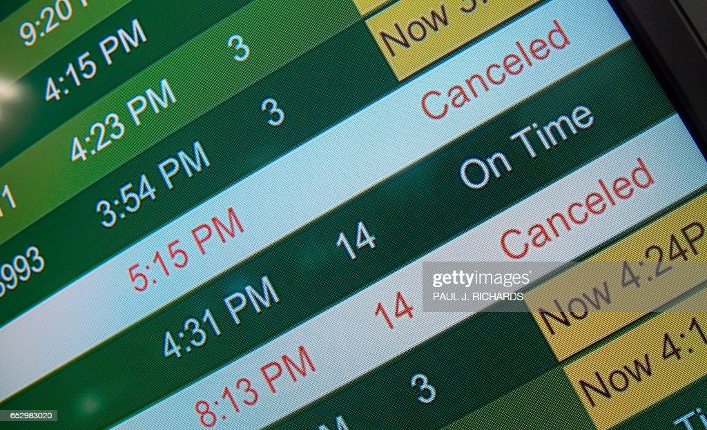 The filght status board is seen at Dulles International Airport (IAD) in Chantilly, Virginia, outside Washington, DC, March 13, 2017, as flights are cancelled in advance of an approaching large snow storm. Millions of Americans braced for potentially the worst winter storm of the season with blizzards forecast to dump up to two feet of snow on the East Coast, closing schools and spelling travel chaos. / AFP PHOTO / Paul J. Richards