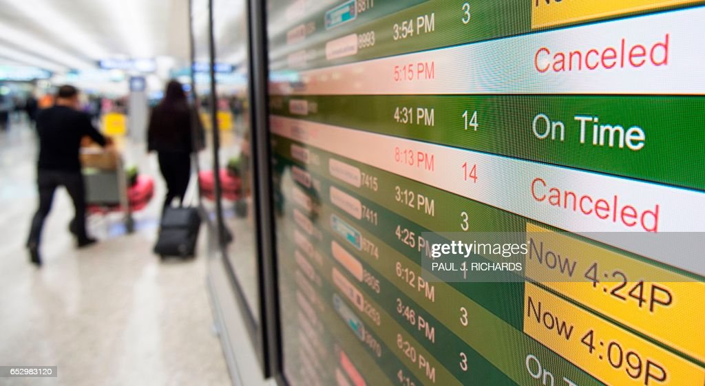 The filght status board is seen at Dulles International Airport (IAD) in Chantilly, Virginia, outside Washington, DC, March 13, 2017, as flights are cancelled in advance of an approaching large sno...