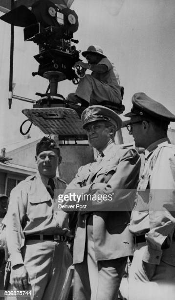 The filming at lowry Stewart Lt Jack Taylor Assistant p i o at lowry Glenn Miller Story Jimmy Stewart confers with two Lawry officers who are...