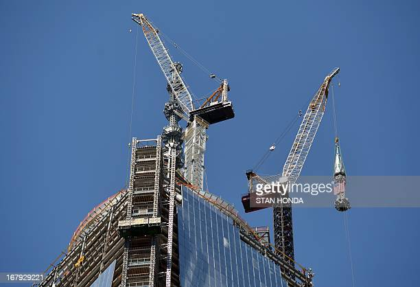 The final sections of the spire is raised to the top of One World Trade Center May 2 2013 in New York to a temporary work platform atop the structure...